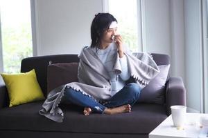 Aziatische vrouwen ziek thuis op de bank foto