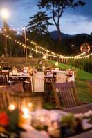 een weergave van een huwelijksceremonie buiten in de tuin foto