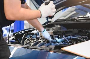 mannelijke monteur houdt zaklamp om auto te onderzoeken