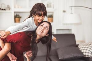 moeder geeft dochter een ritje op de rug
