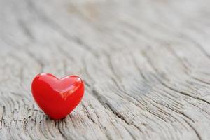 kleine keramische hart zit bovenop houten vloer foto