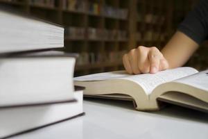 sluit omhoog van een persoon die bij een bibliotheek leest
