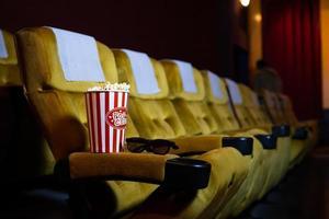 popcorn en glazen op een stoel in een theater foto