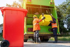 twee vuilnismannen die samenwerken foto
