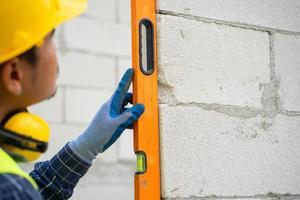 bijgesneden opname van een bouwvakker niveau controleren op bakstenen muur foto