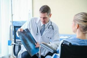 de arts laat de patiënt in de kliniek zien en legt uit wat het resultaat van de röntgenfoto is.