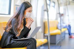 jonge zakenvrouw draagt een gezichtsmasker op de trein foto