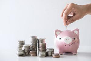 close-up van de hand geld steken in spaarvarken foto