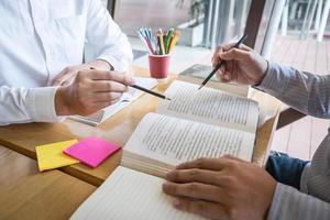 twee mensen studeren en wijzend op tekst op boek foto