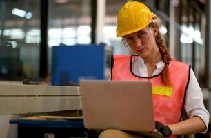 vrouwelijke Kaukasische ingenieur met behulp van laptop in fabriekswerkplaats foto