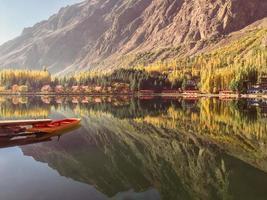 mening van gedokte boot op stilstaand water met bergen op achtergrond