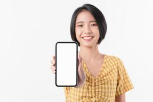 Aziatische vrouw die smartphone op witte achtergrond standhoudt