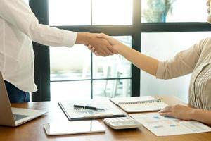 twee professionals ontmoeten elkaar en schudden elkaar de hand foto