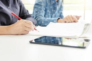 twee mensen studeren samen met telefoon op de voorgrond foto