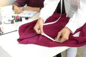 twee kledingmakers die een kledingstuk aanpassen foto