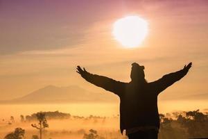 silhouet van vrouwen met opgeheven armen voor zonsondergang foto