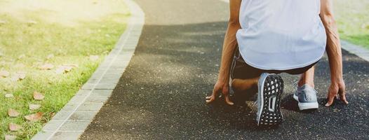 atleet in het runnen van start pose in openbaar park