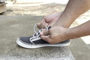 persoon die zijn schoenen bindt