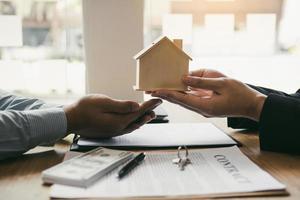 makelaar overhandigt houten huis aan de klant foto