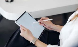 vrouwelijke hand schrijven op tablet foto