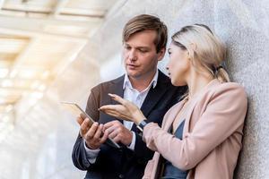 twee zakelijke professionals hebben discussie met behulp van tablet