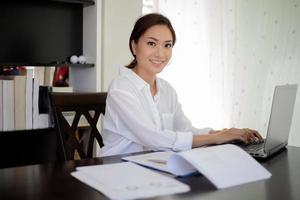 Aziatische zakenvrouw werkt in kantoor aan huis