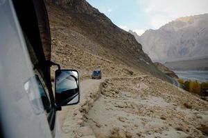 mensen rijden off-road voertuig langs karakoram berg foto