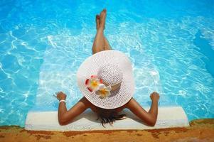 vrouw in witte hoed loungen in het zwembad foto