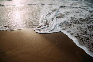 glimmende golven wassen op het strand foto