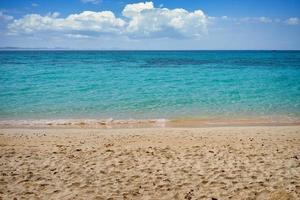 strand en water met bewolkte blauwe hemel
