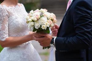 close-up van bruid en bruidegom hand in hand foto