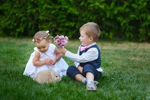 jonge jongen geeft jong meisje een boeket bloemen foto