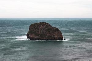 bruine rotsformatie op zee onder witte hemel