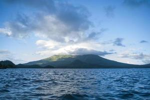 oceaan in de buurt van berg met wolken