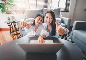 Aziatische vrouwenvrienden die laptop met behulp van die duimen omhoog gebaar geven