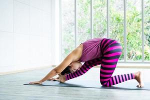 Aziatische vrouw het beoefenen van yoga strekt zich uit foto