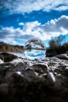 glazen bol op rotsen met blauwe hemel