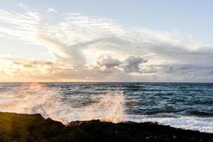 beukende golven op rotsen foto