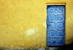 blauwe deur op een gele muur