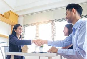 zakenvrouw en klanten schudden elkaar de hand