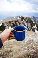 hand met blauwe koffie en mok foto