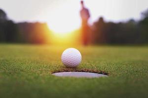 een persoon achter een golfbal op een groen grasveld foto