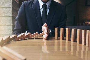 Sluit omhoog van zakenmanhand die dalende houten blokken tegenhouden foto