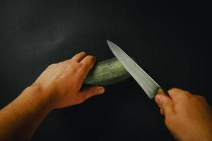 twee handen en mes een komkommer snijden
