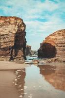 grote rotsen op het strand met bewolkte blauwe hemel