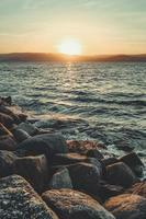 rotsen, water en bergen bij zonsopgang foto