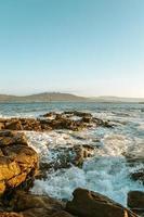 water dat op rotsen bij een kust breekt