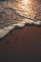 schuimend water stroomt op zand en strand foto