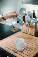 hand met mokka pot boven koffiemok foto