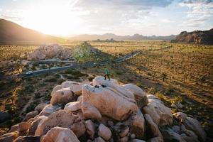 man lopen op rots stapel in Joshua Tree National Park
